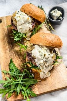 Huisgemaakte hamburger met blauwe kaas, gemarmerd rundvlees, uienmarmelade en rucola
