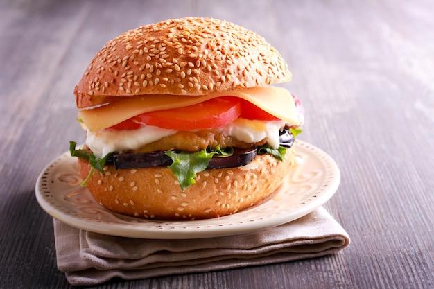 Huisgemaakte hamburger met kip, aubergine, tomaat en kaas