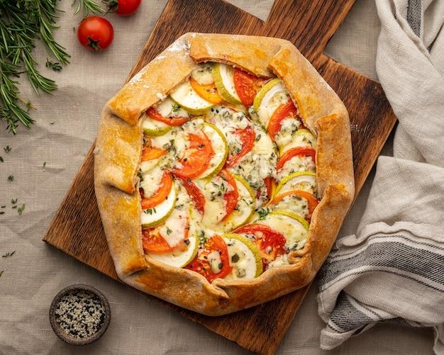 Huisgemaakte hartige galette met groenten, tarwetaart met tomaten, courgette, blauwe kaas gorgonzola. rustieke korstcrostata op donker linnen textieltafelkleed. bovenaanzicht