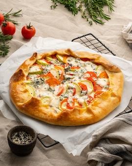 Huisgemaakte hartige galette met groenten, tarwetaart met tomaten, courgette, blauwe kaas gorgonzola. rustieke korstcrostata op donker linnen textieltafelkleed. verticaal