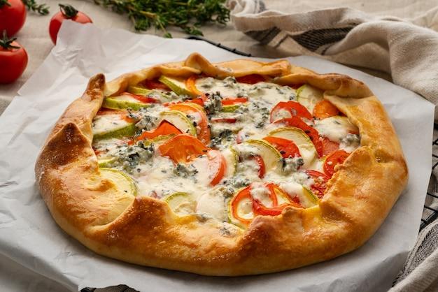 Huisgemaakte hartige galette met groenten, tarwetaart met tomaten, courgette, blauwe kaas gorgonzola. rustieke korstcrostata op donker linnen textieltafelkleed, zijaanzicht