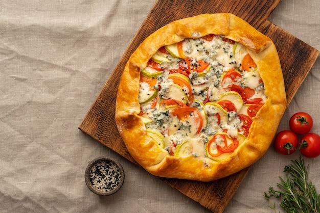Huisgemaakte hartige galette met groenten, tarwetaart met tomaten, courgette, blauwe kaas gorgonzola. rustieke korstcrostata op donker linnen textieltafelkleed.