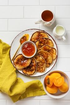 Huisgemaakte heerlijke pannenkoeken met vers abrikozenfruit en jam op een lichte leisteen, stenen of betonnen muur. bovenaanzicht met kopie ruimte.