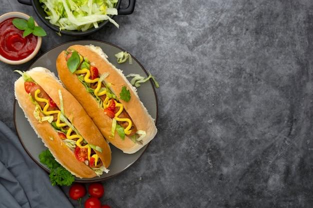 Huisgemaakte hotdogsandwiches. hotdogs met mosterd en sla topping op een donkere achtergrond. ruimte kopiëren