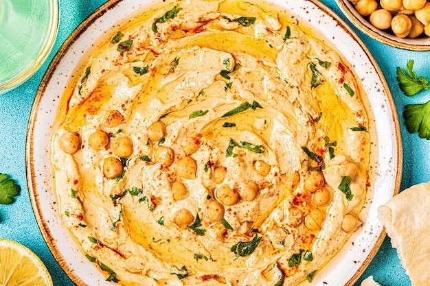 Huisgemaakte hummus gegarneerd met peterselie en geserveerd met pitabroodje