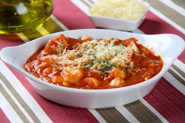 Huisgemaakte italiaanse gnocchi met rode saus en kaas.