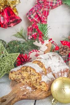 Huisgemaakte kerststolcake met poedersuiker, marsepein en rozijnen.