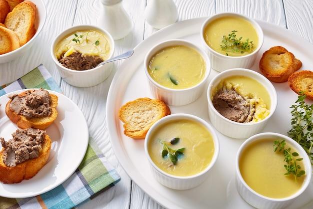 Huisgemaakte kippenleverpastei met kruiden en boter in vormpjes op een schotel met geroosterde plakjes stokbrood en paté lever sandwiches
