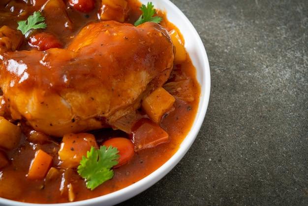 Huisgemaakte kippenstoofpot met tomaten, uien, wortel en aardappelen op bord