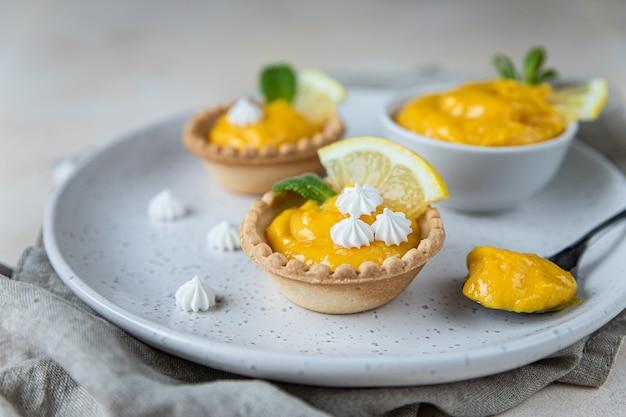 Huisgemaakte lemon curd in taartjes met schijfjes citroen mini meringue en munt
