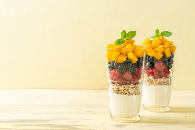 Huisgemaakte mango, framboos en bosbessen met yoghurt en granola - gezonde voeding