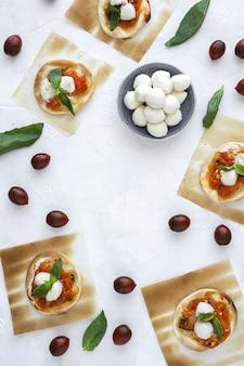 Huisgemaakte minipizza's margarita met tomaat, mozzarella en basilicum