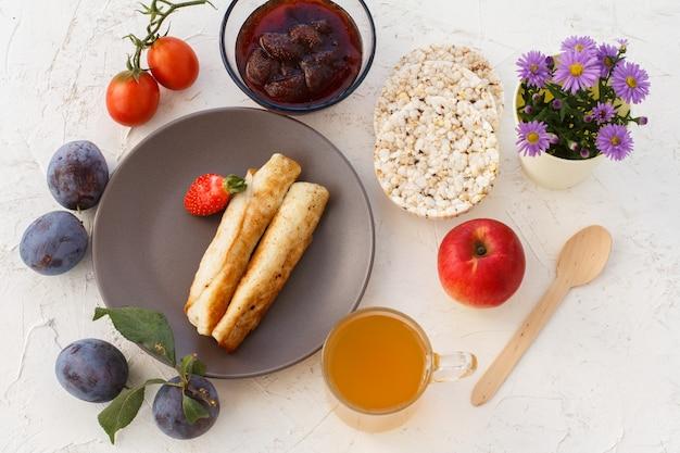 Huisgemaakte pannenkoeken gevuld met kwark, een aardbei op het bord, pruimen, een glazen kom met jam, een houten lepel, appels, gepofte rijstwafels, een kopje thee en bloemen. bovenaanzicht.