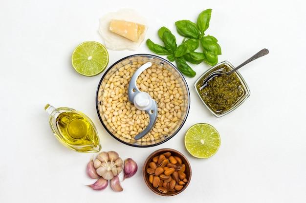 Huisgemaakte pestosaus en ingrediënten. snijder met pijnboompitten, ongeschilde pijnboompitten in kom, olijfolie, pestokom, basilicumblaadjes, parmezaan, knoflook, citroen. plat leggen. witte achtergrond