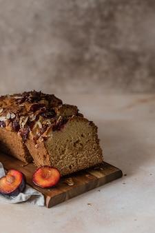 Huisgemaakte pittige pruimencake versierd met amandel op een houten serveerplank