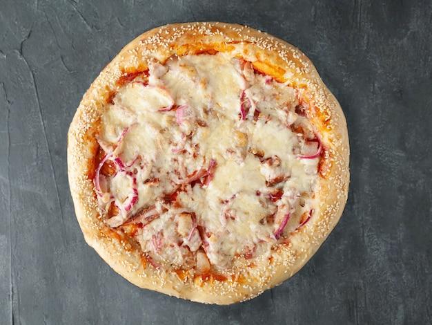 Huisgemaakte pizza met ham en plakjes bacon, mozzarella en parmezaanse kaas, ingelegde rode ui en tomatensaus. brede kant. uitzicht van boven. op een grijze betonnen achtergrond. geïsoleerd.