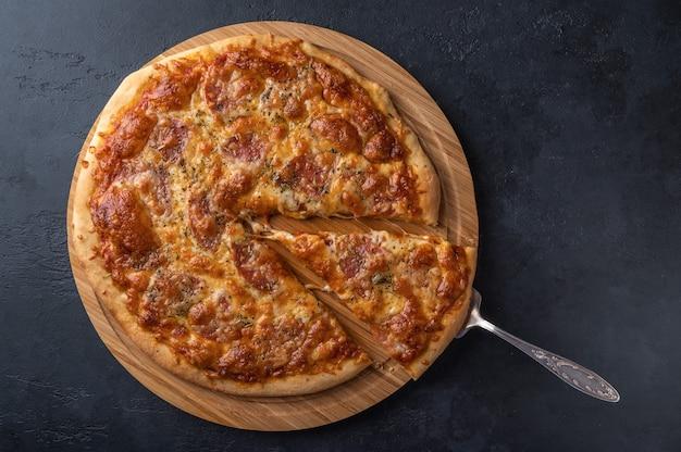 Huisgemaakte pizza met mozzarella, salami en kruiden.