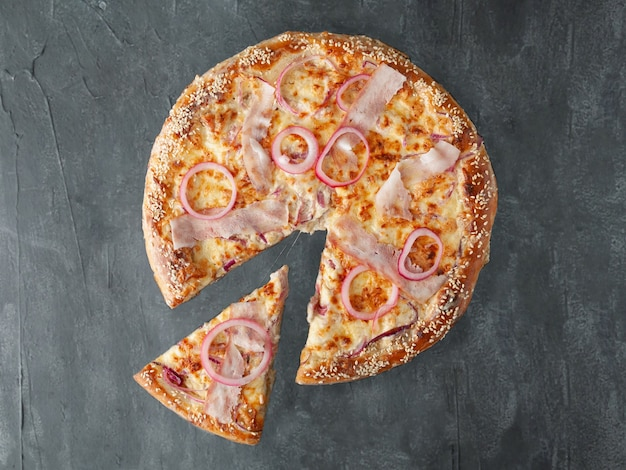 Huisgemaakte pizza met plakjes bacon, ingelegde rode ui, mozzarella kaas, parmezaanse kaas en tomatensaus. van pizza wordt een stuk afgesneden. uitzicht van boven. op een grijze betonnen achtergrond. geïsoleerd.