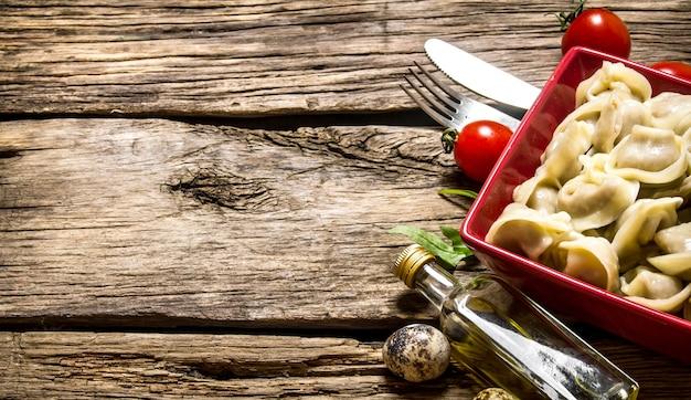 Huisgemaakte ravioli bereid met tomaten en olijfolie. op de houten achtergrond. vrije ruimte voor tekst.