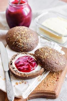Huisgemaakte roggebroodjes met lijnzaad, sesam en maanzaad geserveerd met boter en jostaberryjam