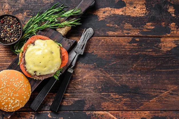 Huisgemaakte runderburgers met kaas, bladgroente en ui