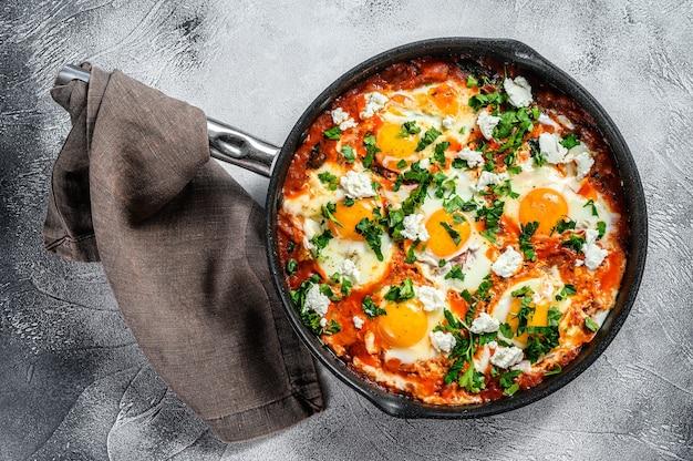 Huisgemaakte shakshuka, gebakken eieren, ui, paprika, tomaten en peterselie in een pan. grijze achtergrond. bovenaanzicht.