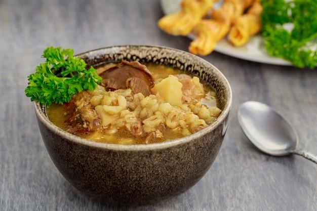 Huisgemaakte soep met champignons, gerst en crackers.