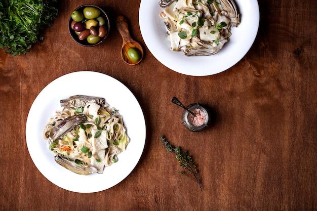 Huisgemaakte tagliatelle met artisjokken en inktvis in roomsaus
