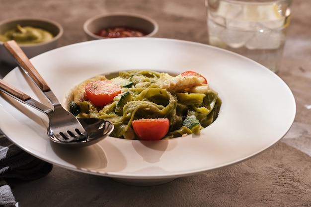 Huisgemaakte tagliatelle pasta met courgette, tomaten en kabeljauw