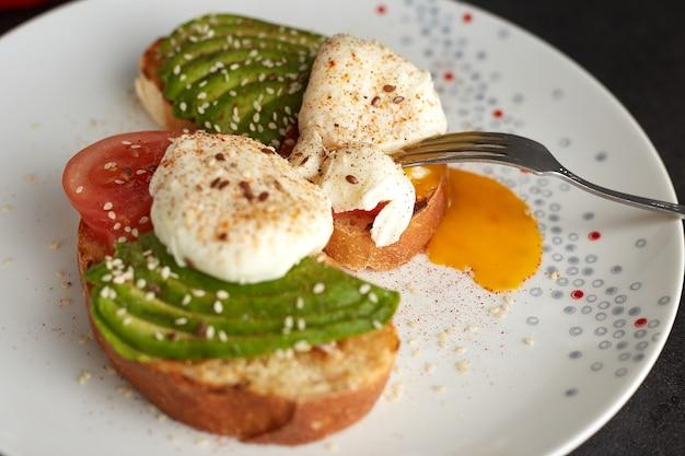 Huisgemaakte toast met avocado, gepocheerde eieren, tomaat en zaden. gezond eten