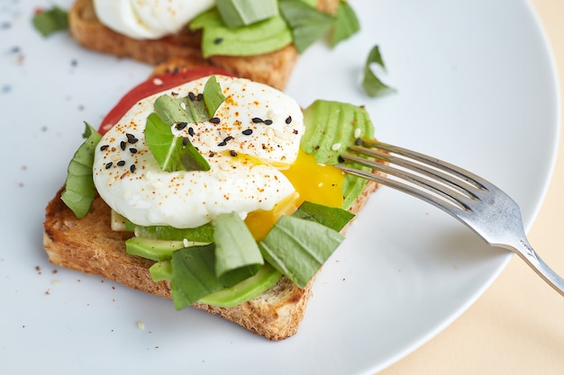 Huisgemaakte toast met avocado, gepocheerde eieren, tomaat en zaden