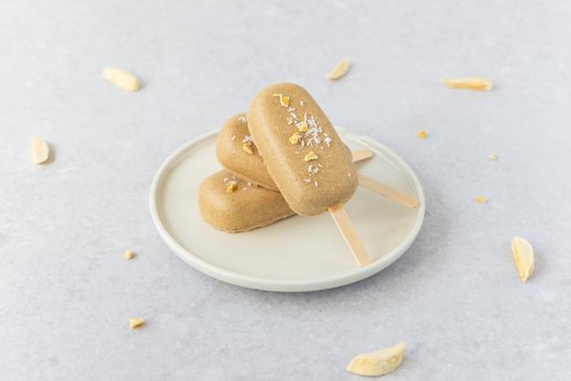 Huisgemaakte vegan ijslolly met chocolade cashewnoten op een bord