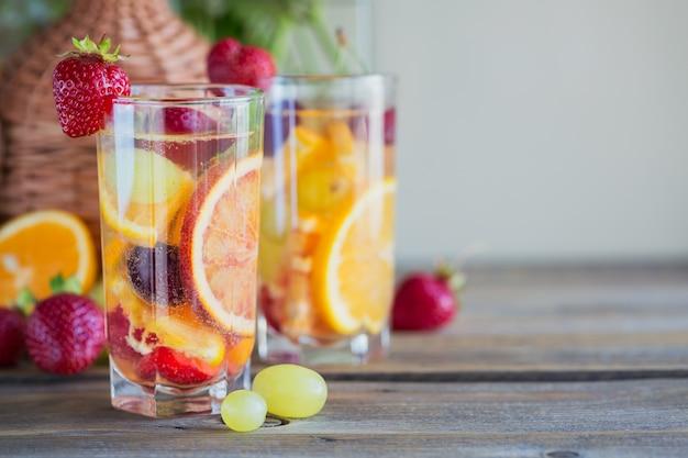 Huisgemaakte verfrissende fruitsangria of punch met champagne, aardbeien, sinaasappels en druiven