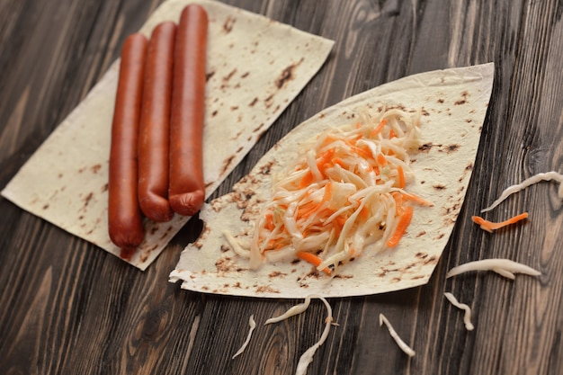 Huisgemaakte worst, pitabroodje en zuurkool voor het maken van shoarma.