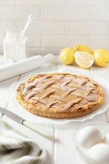 Huisgemaakte zandkoek-citroentaart met een rieten patroon bestrooid met poedersuiker.