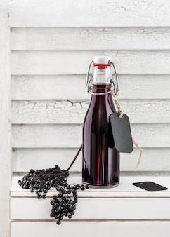 Huisgemaakte zwarte vlierbessensiroop in een klein glazen flesje
