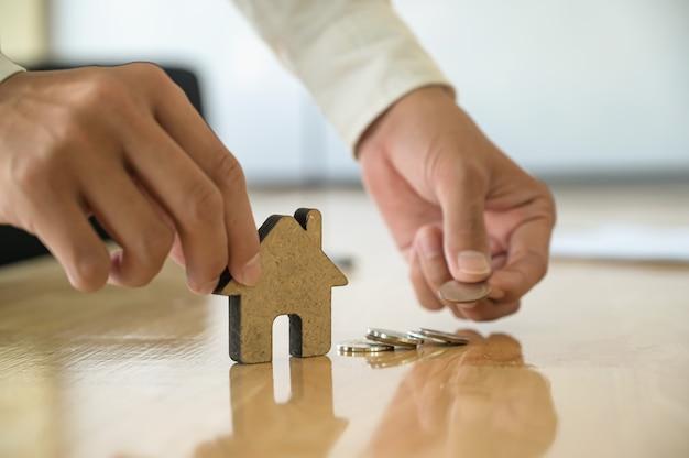 Huishandelconcept, de hand van mensen die een huismodel houden dat van hout en muntstukken wordt gemaakt.