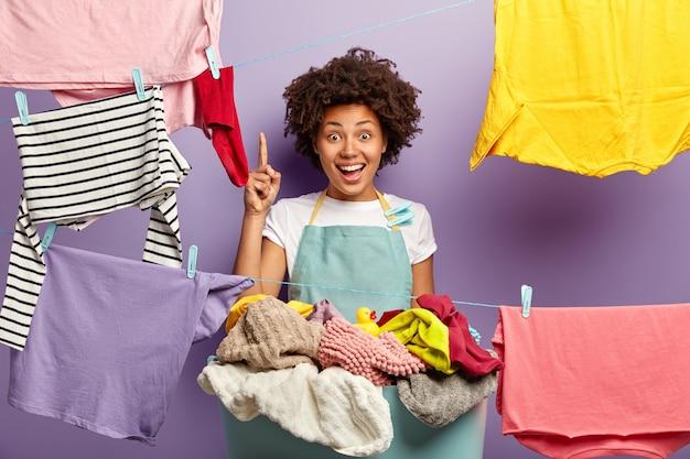 Huishoud- en wasconcept. gelukkig donkere vrouwelijke huishoudster draagt een schort