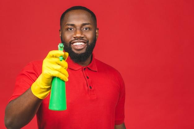 Huishoudelijk concept. jonge afro-amerikaanse man schoonmaken met handschoenen