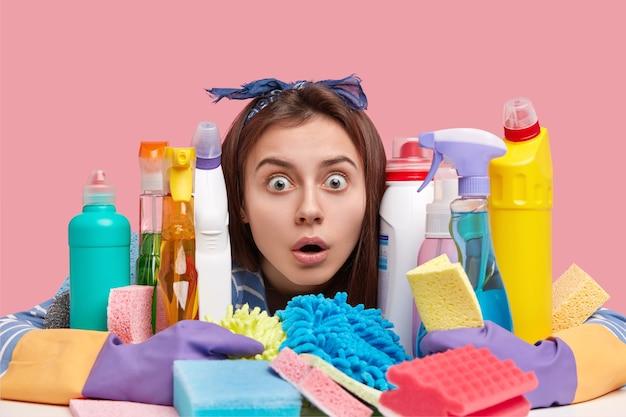 Huishoudelijk concept. verbaasd donkerharige vrouw staart door flessen afwasmiddel, gebruikt wasmiddel voor microvave-oven en fornuizen