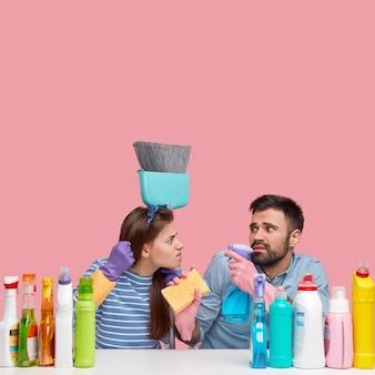 Huishoudelijk werk concept. boze huisvrouw toont vuist en drukt woede uit naar echtgenoot, eist huishoudelijk werk, gebruikt verschillende schoonmaakproducten, houdt bezem, spray en spons vast, geïsoleerd op roze muur