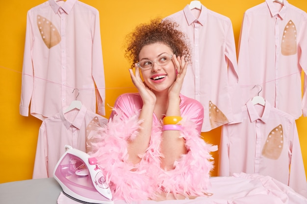 Huishoudelijk werk en huishouden concept. tevreden dromerige vrouw met krullend haar draagt transparante bril en kamerjas kijkt met dromerige uitdrukking opzij strijkt kleren aan boord. gelukkige huisvrouw