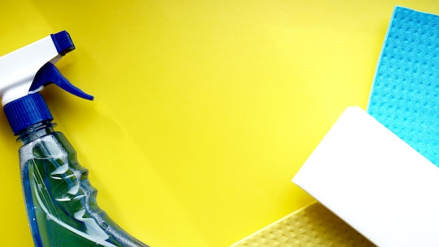 Huishoudelijk werk, huishouden en huishoudelijk concept - reinigingsdoek, wasmiddelspray op gele achtergrond