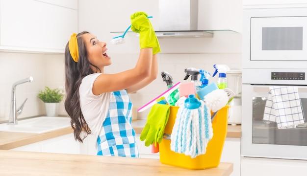 Huishoudelijke jongedame met een gele emmer vol schoonmaakspullen op haar keukenbureau en doet stoeien met een keukenborstel die doet alsof ze erin zingt.