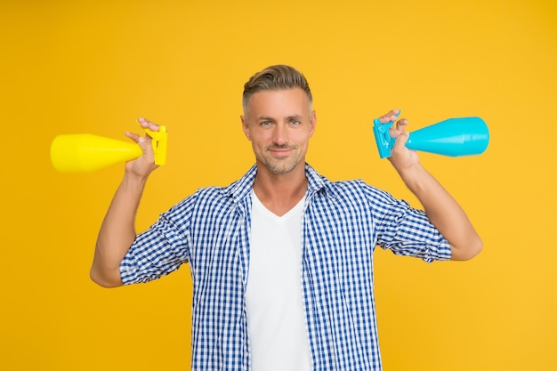 Huishoudelijke schoonmaakmiddelen doden het coronavirus. gelukkige kerel houdt spuitflessen vast. gebruik van huishoudelijke schoonmaakmiddelen en ontsmettingsmiddelen. huishoudelijke hygiëne. routinematige reiniging en desinfectie van het huishouden.