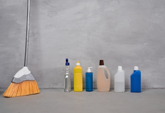 Huishoudelijke schoonmaakproducten en gereedschap bezemflessen met verschillende wasmiddelen die op de vloer staan