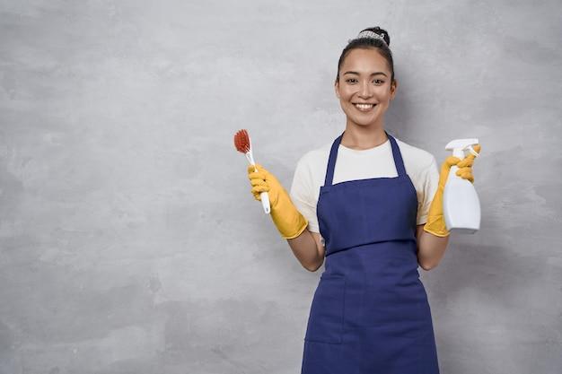 Huishouden en huishoudelijk werk concept. portret van een gelukkige jonge vrouw, mooie schoonmaakster in uniform met schoonmaakborstel en spray, glimlachend in de camera terwijl ze tegen een grijze muur staat. huiswerk