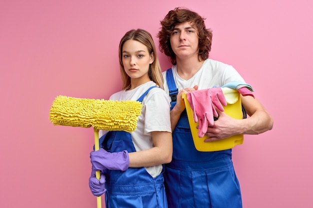 Huishouding concept. zelfverzekerde man en vrouw met schoonmaakbenodigdheden in handen beginnen met schoonmaken in huis