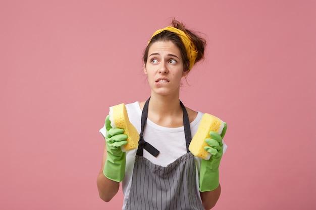 Huishouding, huishoudelijk werk, hygiëne en netheid. gefrustreerde jonge vrouw in schort en beschermende handschoenen die op haar lip bijten, zich gestrest voelen omdat ze de kamers niet haalt voordat de gasten komen