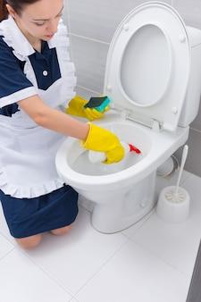 Huishoudster besproeit de binnenkant van een toiletpot met een antibacterieel reinigingsmiddel terwijl ze een hotelbadkamer schoonmaakt en onderhoudt